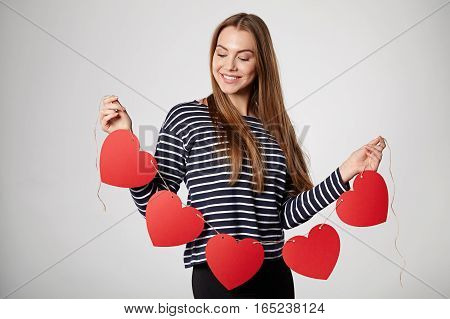 Beautiful smiling woman holding garland of five red paper hearts shape - blank copy space for letters or text, looking down at hearts