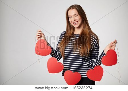 Playful smiling woman holding garland of five red paper hearts shape - blank copy space for letters or text, looking at camera and winking