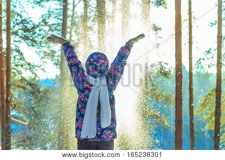 Girl throws snow in sunny winter forest