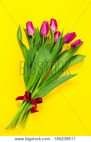 Bouquet of fresh beautiful lila tulips on yellow colorful background. Spring concept. Horizontal top view with copy space.