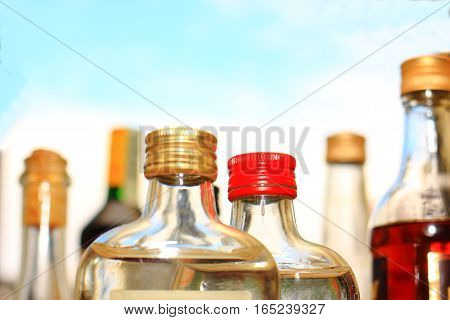 Bottles with alcohol and colored lids on a light background