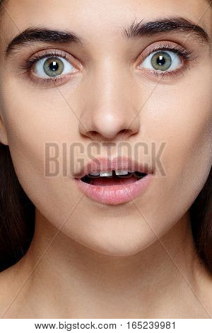 people luxury and fashion emotions concept - Portrait of young woman with shocked facial expression Closeup of beautiful brunette woman with pretty eyes and gap between teeth