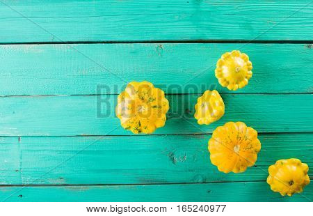 Yellow squash on a wooden turquoise background. Top view Colorful festive still life. Copyspace.