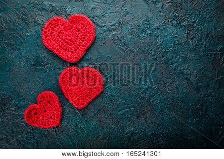 Three crochet valentine hearts on dark background.
