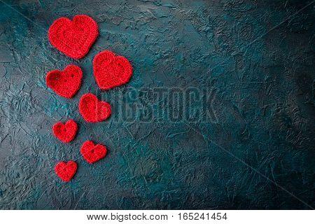 Red crochet valentine hearts on dark background.