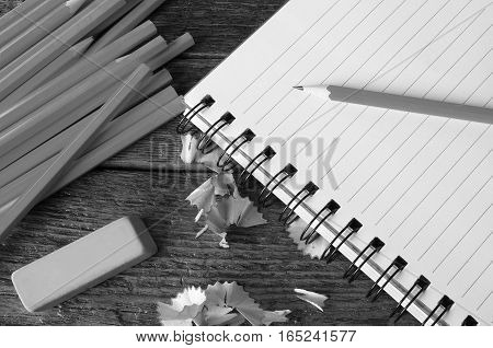 A black and white image of an open notebook and several wooden pencils.