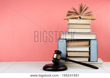 Old hardback books, diary, fanned pages on wooden deck table and pink background. Books stacking. Copy Space. Education Law background.