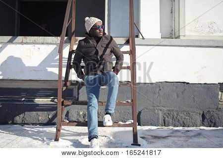 Fashion Stylish Young African Man Wearing A Jacket Hat Over Urban Background, Winter Street Style