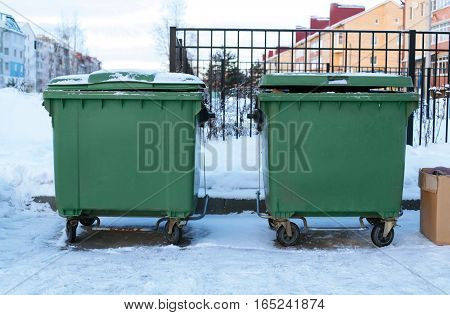 Garbage cans with trash on street winter