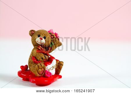 Bear figurine on Hearts Valentine's Day. on pink blurry background