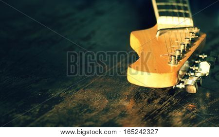 Electric guitar neck on a wooden background.