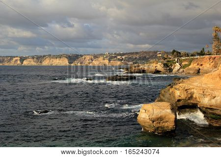 Image of seashore, with jagged cliffs and waves crashing against them