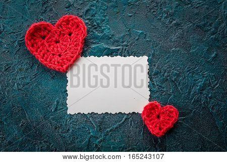 Three crochet valentine hearts and greeting card on dark background.