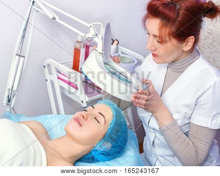 young woman in spa salon with beautician. Cosmetologist looking through a magnifying glass at her client and doing a professional cosmetology procedures for young woman with fresh and clean skin