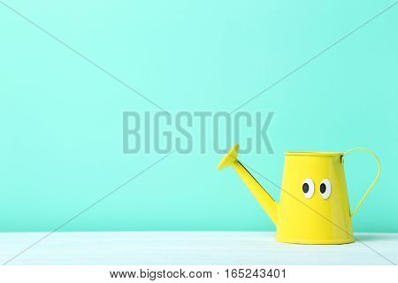 Yellow Watering Can With Googly Eyes On A Green Background