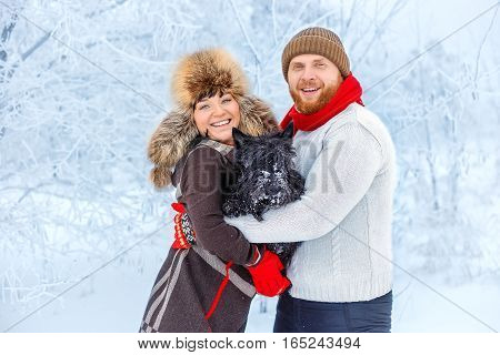 portrait of happy winter couple with pet small dog scottish terrier. Young man and woman in love with dog walking in the snowy forest. Family playing with dog outdoor