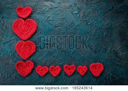 Red crochet valentine hearts on dark bacground.