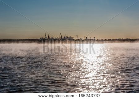 River landscape with fog during sunrise. Glittering water. Old barge background.