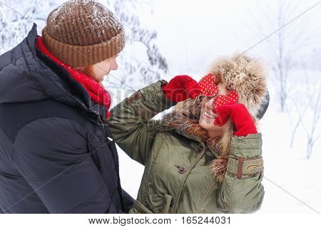 Love story in the winter forest with red hearts. Young romantic couple outdoor. Happy couple in winter clothes. Winter love story. Valentine's Day and love concept. Girl holding red hearts cover eyes