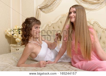 Two girlfriends on a large bed rest
