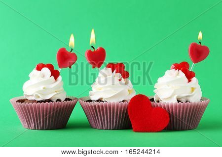Tasty Cupcakes With Candles On Green Background