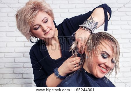 hairdresser giving a new haircut to female customer. Hairdresser cut hair. Happy woman getting stylish haircut by hairdresser. Women's haircut. Process of hair cutting with use thinning scissors