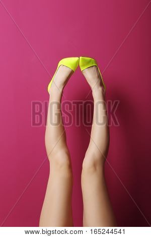 Female Legs With Yellow High Heels On A Pink Background