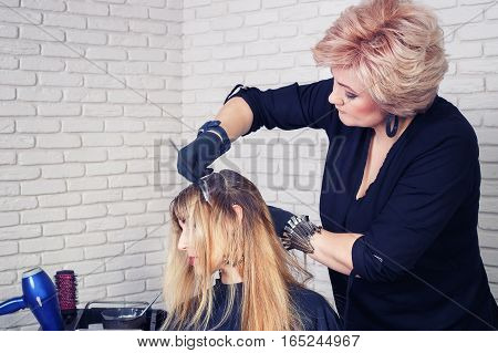 Hair salon. Hair coloring in process. Stylist working with hair. Hairdresser coloring hair in studio. Professional female hairdresser applying color to customer at hair salon. Photo with toning