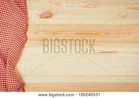 Top view of red checkered napkin or tablecloth on raw wooden table with visible planks, texture and copy space for text.
