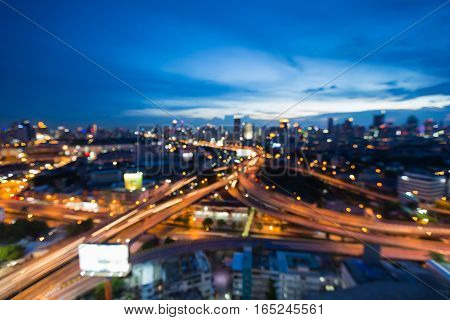 Blurred light highway interchanged with city downtown twilight skyline background