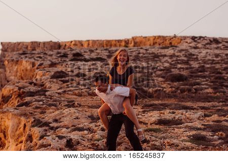 Man Carry Woman On Back In The Evening On The Rock