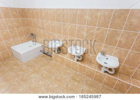 Clean children washroom with sinks and water-closet in kindergarten.