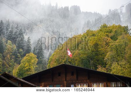 Swiss flag on wood house - stock photo