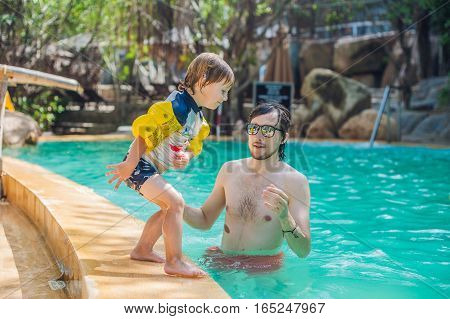 Young Cheerful Father And Son In A Swimming Pool