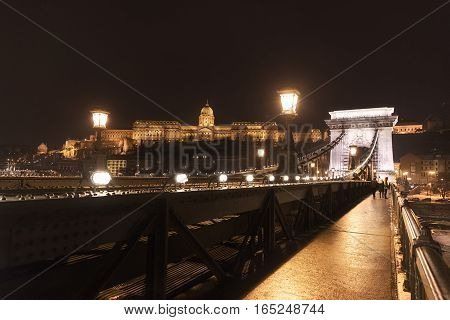 Chainbridge at nighttime with Castle of Buda photo