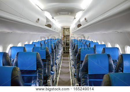 Angle shot of an airplane corridor with blue seats
