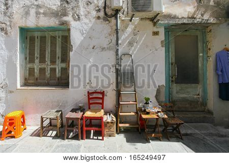 Rethymnon Island Crete Greece - June 23 2016: Wooden chairs ladder small tables with cups of frappe near the outside wall of old house located in Old Town of Rethymnon