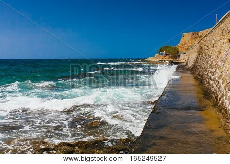 Rethymnon Island Crete Greece - July 1 2016: View on Leoforos Emmanouil Kefalogianni embankment and sea with clear emerald water.