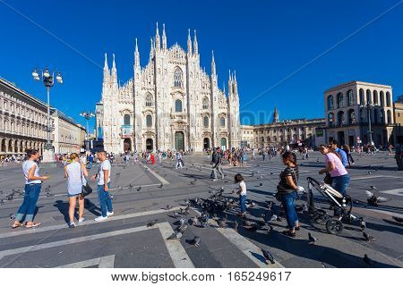 View on the Piazza del Duomo and the Duomo cathedral in Milan. A lot of tourists and pigeons on the Piazza del Duomo