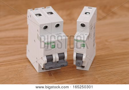 SARANSK, RUSSIA - JANUARY 13, 2017: Schneider Electric one-pole and two-pole circuit breakers on wooden background.
