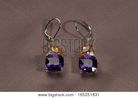 Precious earrings with stones on satin brown background
