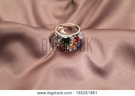 Precious ring with stones on satin brown background
