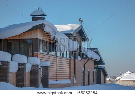 House Covered With A Thick Layer Of Snow And Weather Vane On The Roof
