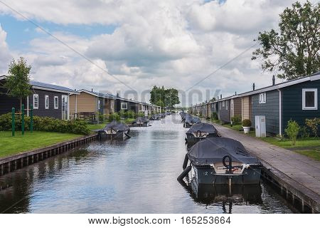 Canal with moored boats near the bungalow.