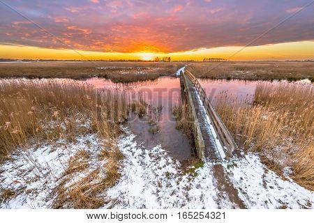 Bridge Crossing River In Snowy Winter Landscape