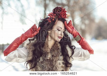 woman in a fur vest, red gloves and a wreath on a background of a winter landscape