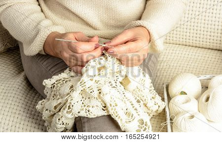 woman sitting on sofa covered with white woolen blanket and crochet tablecloth