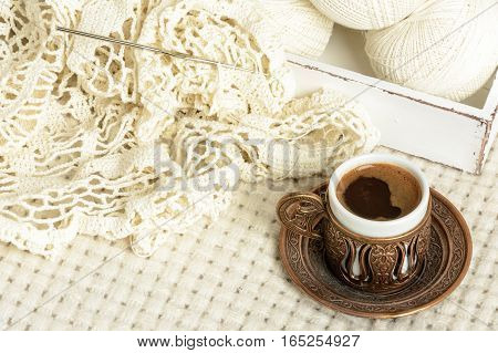 crochet tablecloth crochet hooks balls of cotton thread and cup of black coffee on a white woolen plaid