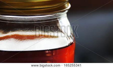 Glass canning jar filled with dark reddish tea.