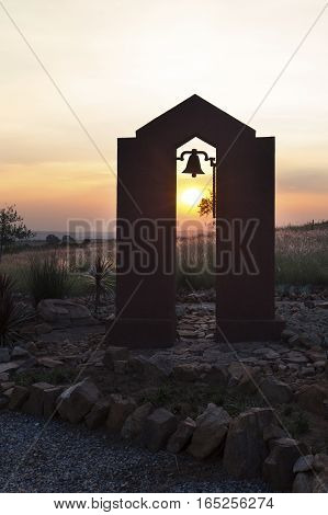 Silhouette at sunset of a bell in an arch along a rocky path